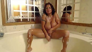 This flexible huge breasted ginger cougar masturbates in the bath like a boss