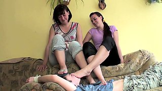 Two dominant babes fulfilling a guy's foot fetish fantasy